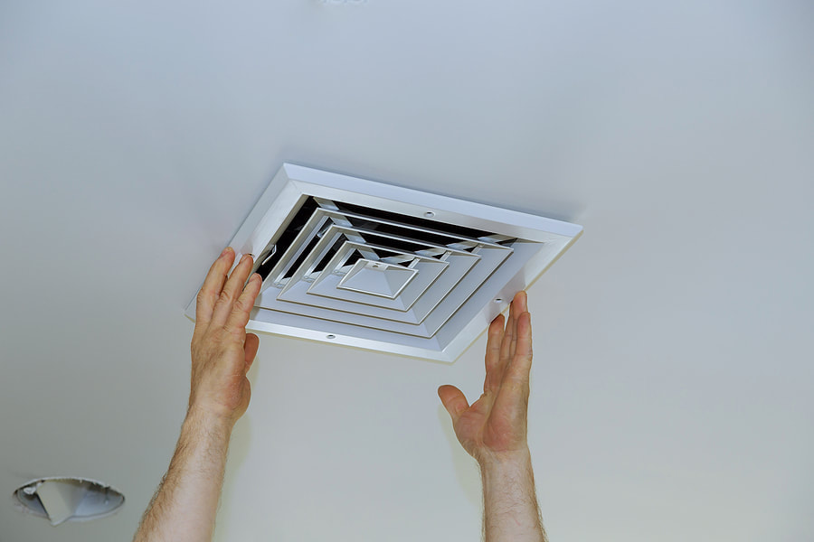 man pulling off an air vent